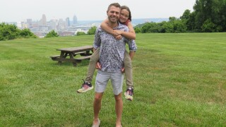 Ryan Joseph Allen holds his daughter, Harper Rae, on his back as they pose for a picture at Children's Home of Northern Kentucky. The Cincinnati skyline is in the background.