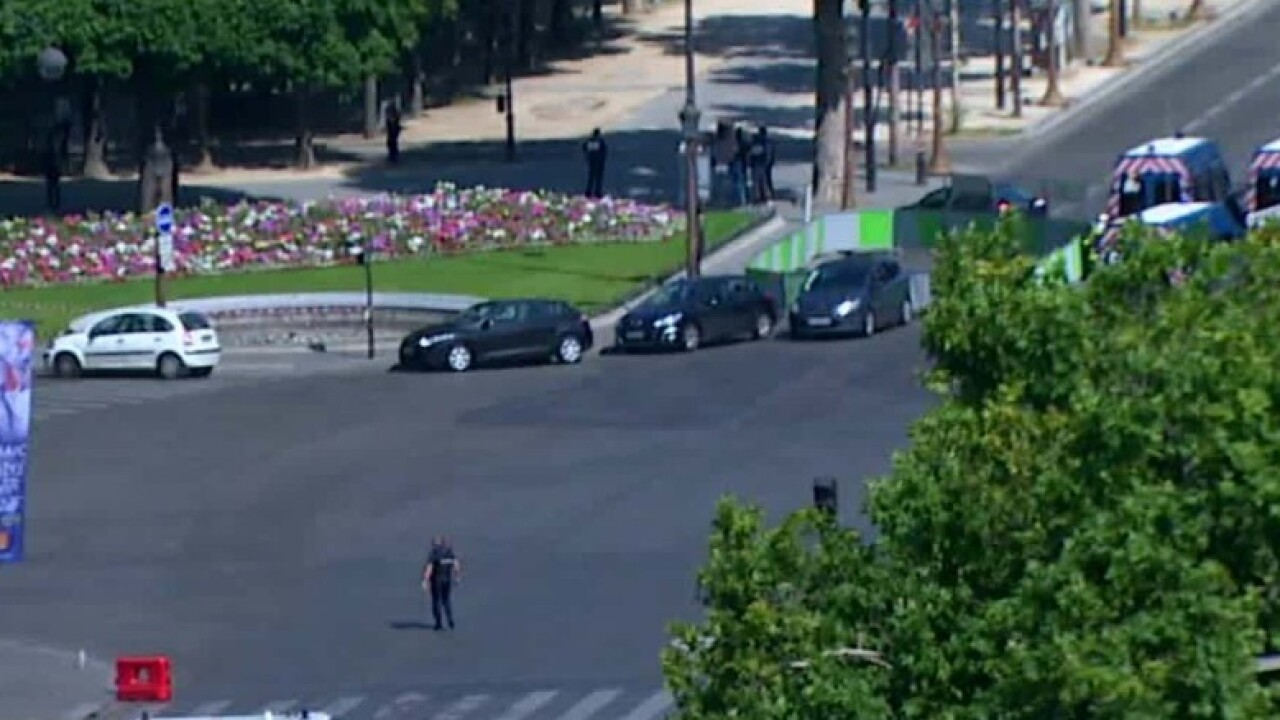 Car rams police van on Champs-Elysees, armed suspect may be dead