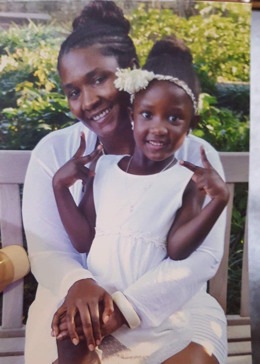 Kendra Davis and her daughter smile in an undated photo. Both are wearing white, and Davis's daughter is sitting on her lap.