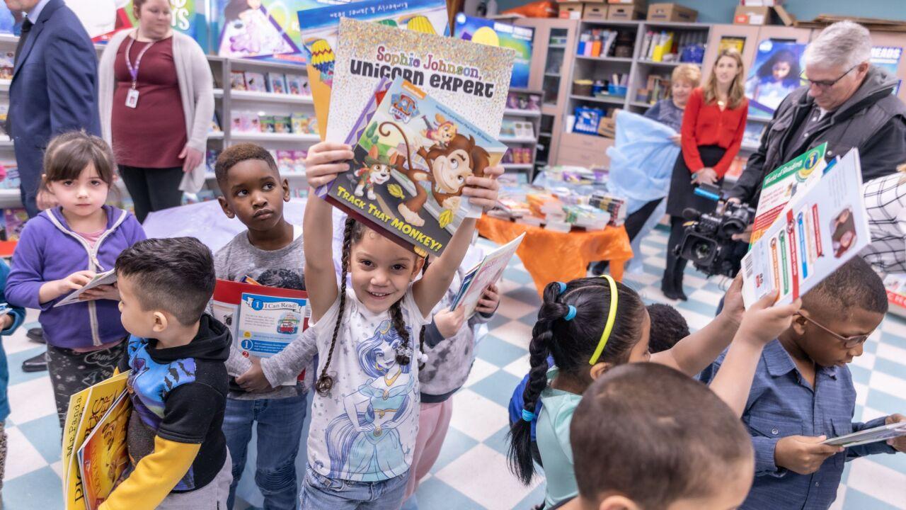 Girl holding books overhead.jpeg