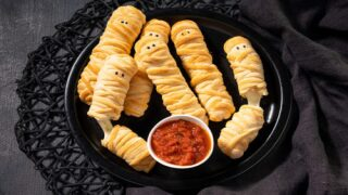 These 3-Ingredient Baked String Cheese 'mummies' Are An Easy Halloween Snack Kids Will Love