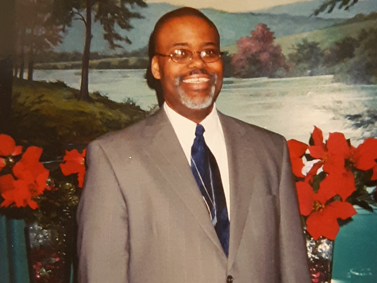Herndon Anderson smiles in an undated photo. He is wearing glasses and is dressed in a white shirt, a blue patterned tie and a grey suit.