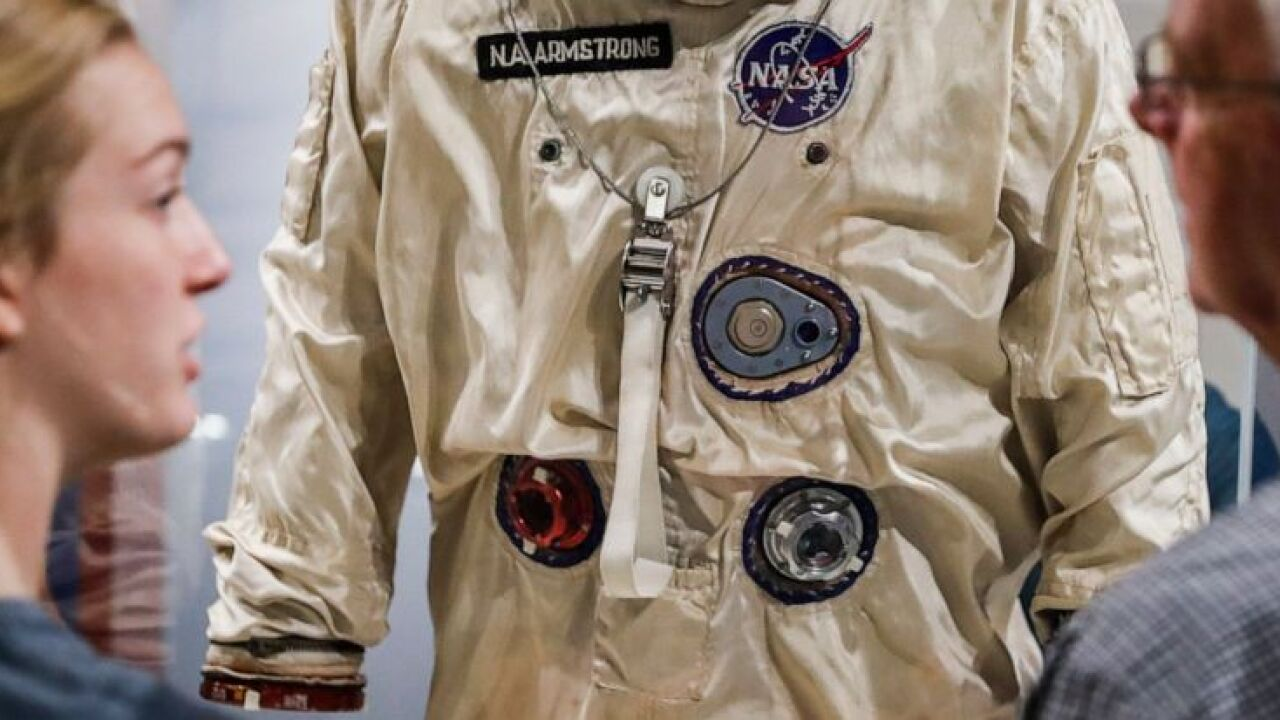 Visitors stand before spacesuit worn by Neil Armstrong (AP Photo/John Minchillo)