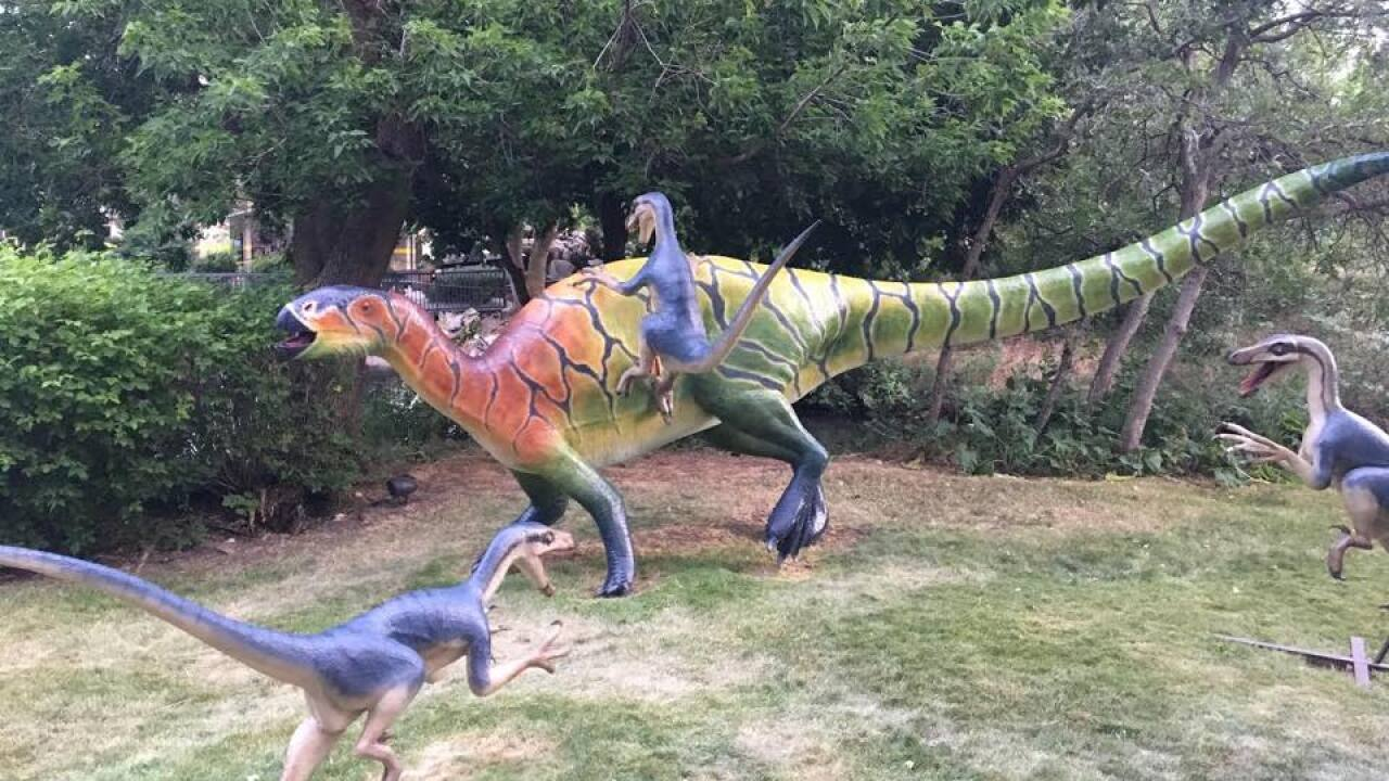 Sculptures at Eccles Dinosaur Park in Ogden, Utah show three raptors attacking a larger dinosaur