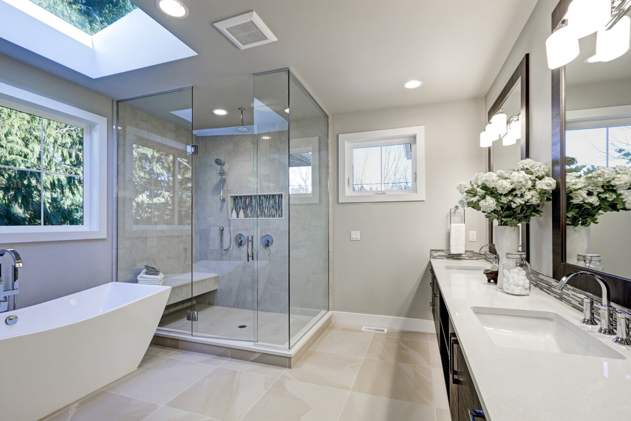 A brightly lit modern bathroom with brand new tile and furnishings.