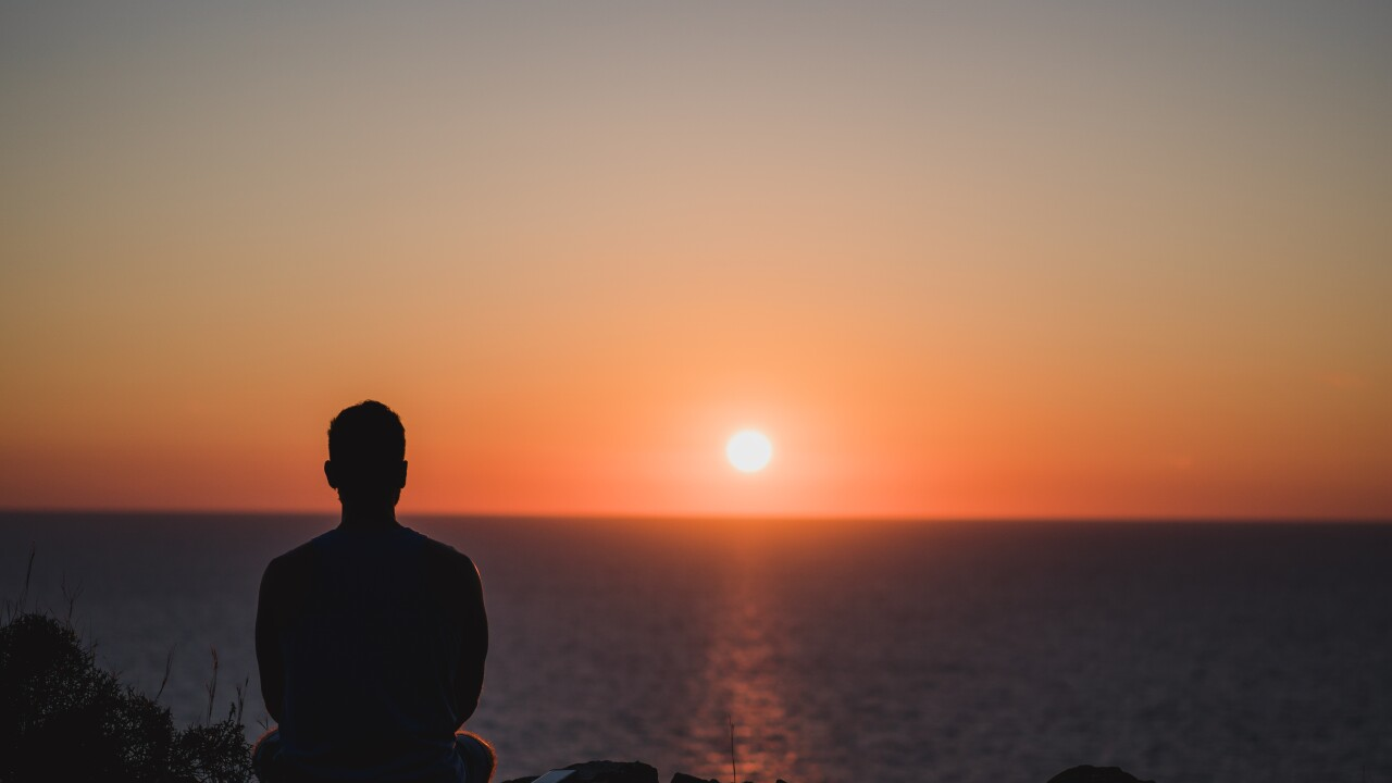 Young man looking to the sunset over sea. Enjoying and relaxing concept, full of unforgettable experiences to recharge. Balance mind and body