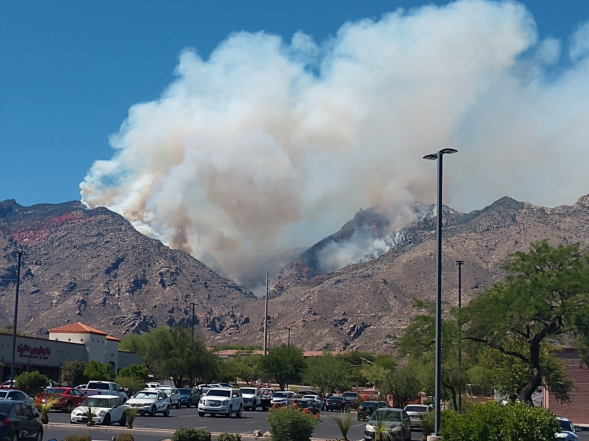 A view of the Bighorn Fire burning in the Catalina Mountains from the Basha's parking lot at Kolb and Sunrise