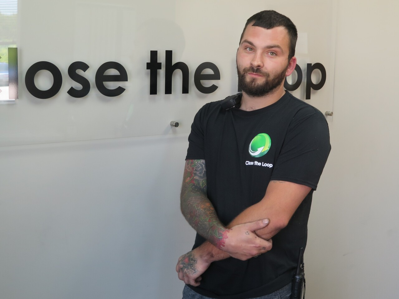 Adam Criss poses for a portrait in the main office of Close the Loop, the company where he works. Criss is wearing a black t-shirt and has his arms crossed in front of him.
