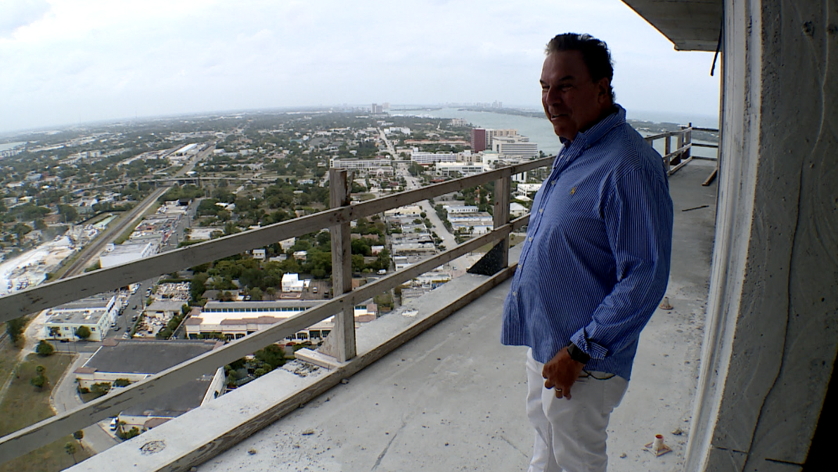 Jeff Greene looks out into West Palm Beach as he stands on unfinished balcony of high-rise towers