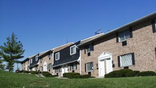 This apartment complex is part of Cincinnati Metropolitan Housing Authority's housing choice voucher program. The buildings have tan brick, white doors and dark shingle roofs.