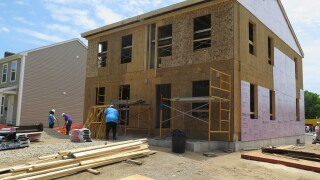 A two-story duplex is under construction in Cincinnati's Bond Hill neighborhood. In this photo, volunteers work on the structure while lumber sits piled up in front of it.