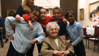 Marian Spencer, seated, in March 2019 with the four Winton Hills Academy students who wrote a book about her. The girls' teacher is pictured, too.