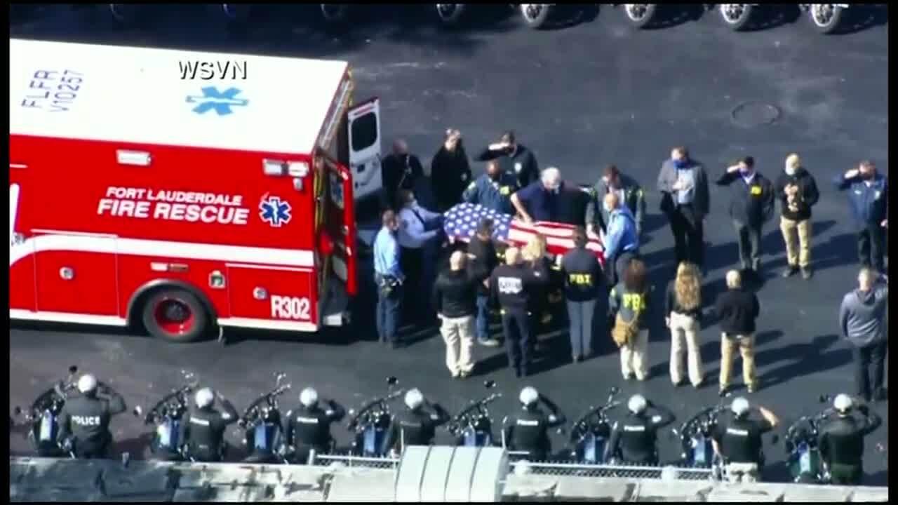 Aerial of U.S. flag draped over casket exiting back of ambulance after FBI shooting