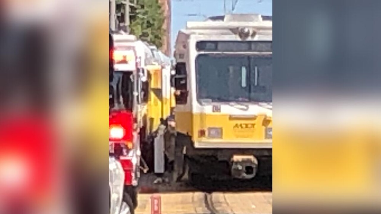 Car wedged between two light rail trains