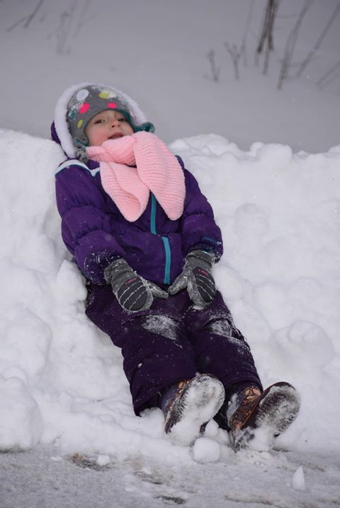Child lying down in the snow