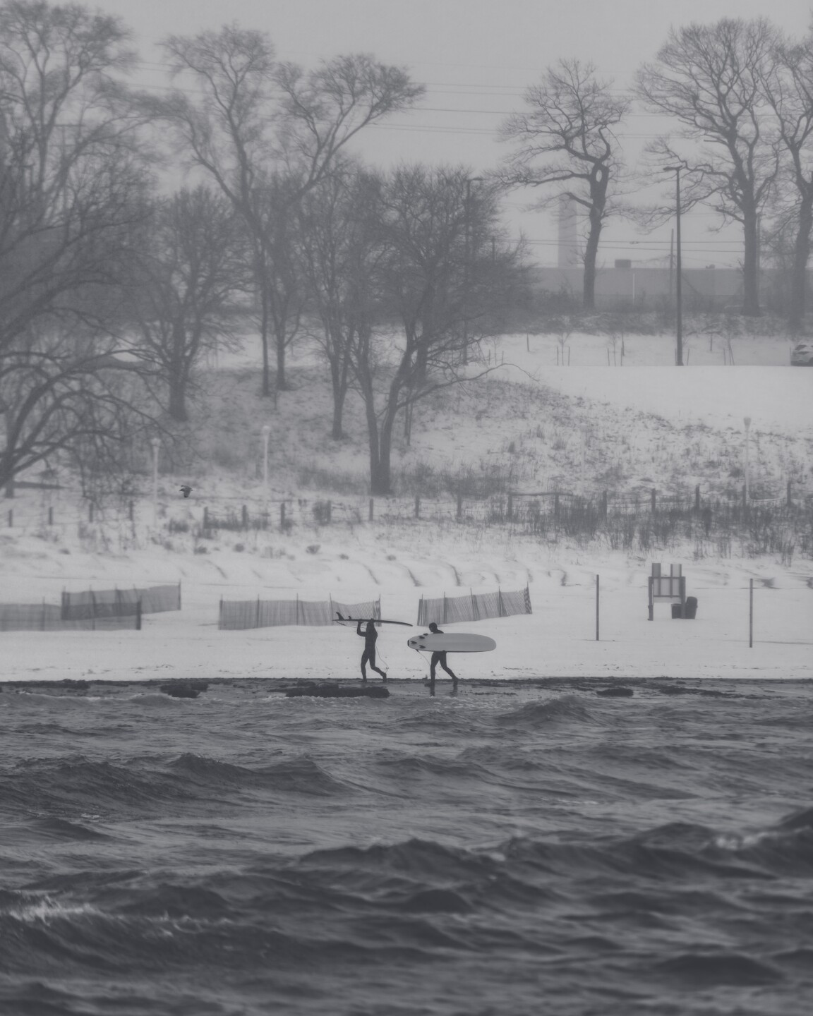 Surfers brave the cold at Edgewater Beach to catch some waves.
