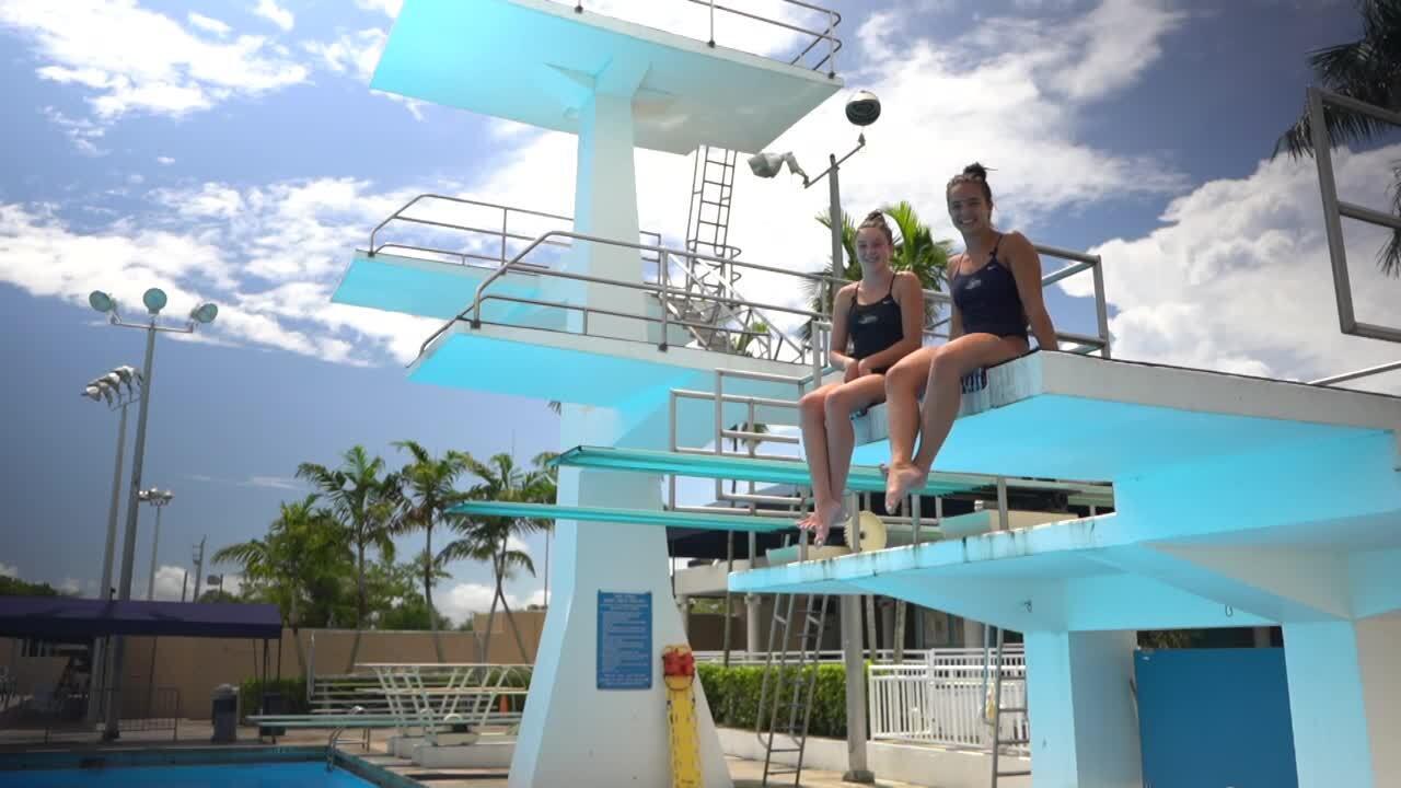 Kaylee Bishop and Emilie Moore sit on high dive at Coral Springs Aquatic Center