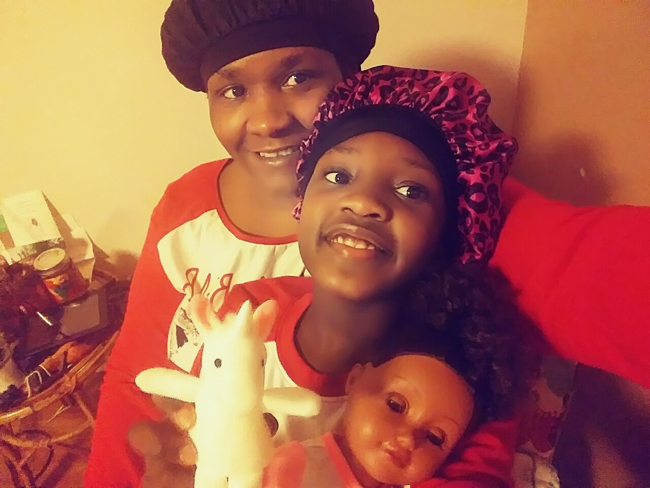 Kendra Davis smiles as she takes a photo with her daughter, who also is smiling and holding a baby doll and unicorn toy.
