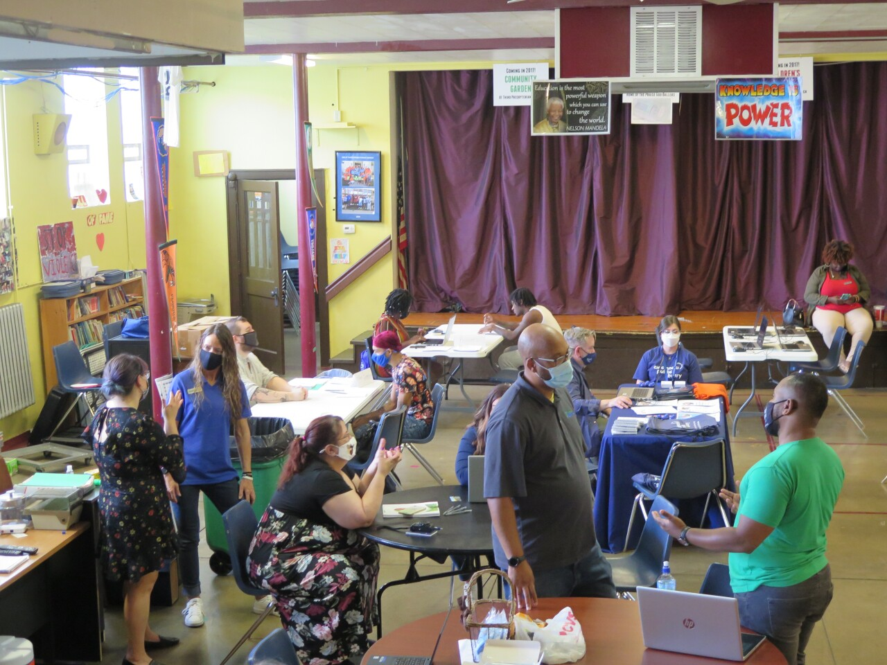 This photo shows the Cincinnati Works workshop and resource fair in East Westwood on Aug. 17, 2021. There are masked people talking with each other and two young people working with Cincinnati Works staff on their resumes and interviewing skills.
