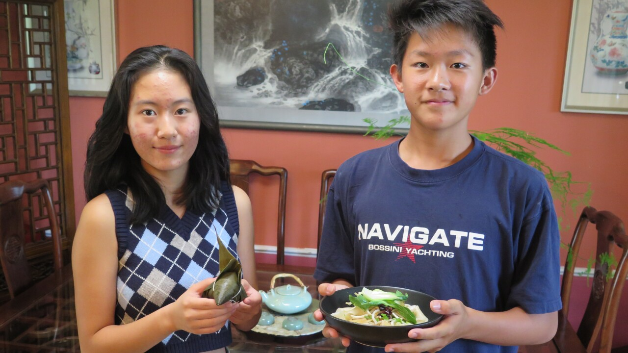 Katherine Wen, left, and Edward Zha pose with the dishes they will be making for the 2021 Asian Food Fest in downtown Cincinnati. Katherine is holding Zongzi, a sticky dumpling wrapped in a reed leaf. Edward is holding a bowl of Biang Biang Mian, a spicy noodle dish.
