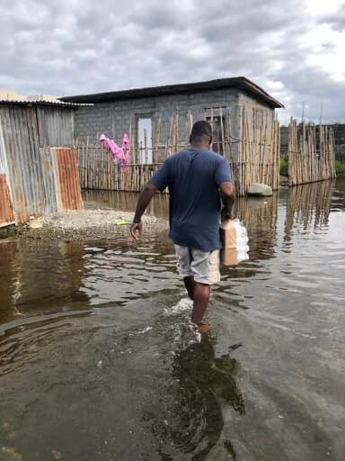 Telsaint Morisset carries water on a trip back to Haiti with his non-profit, Figi Jezi.
