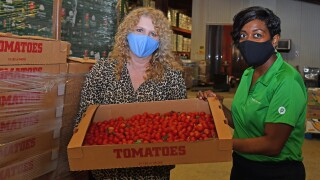 Judy Cruz with Robin Hankerson with tomatoes delivered from Publix