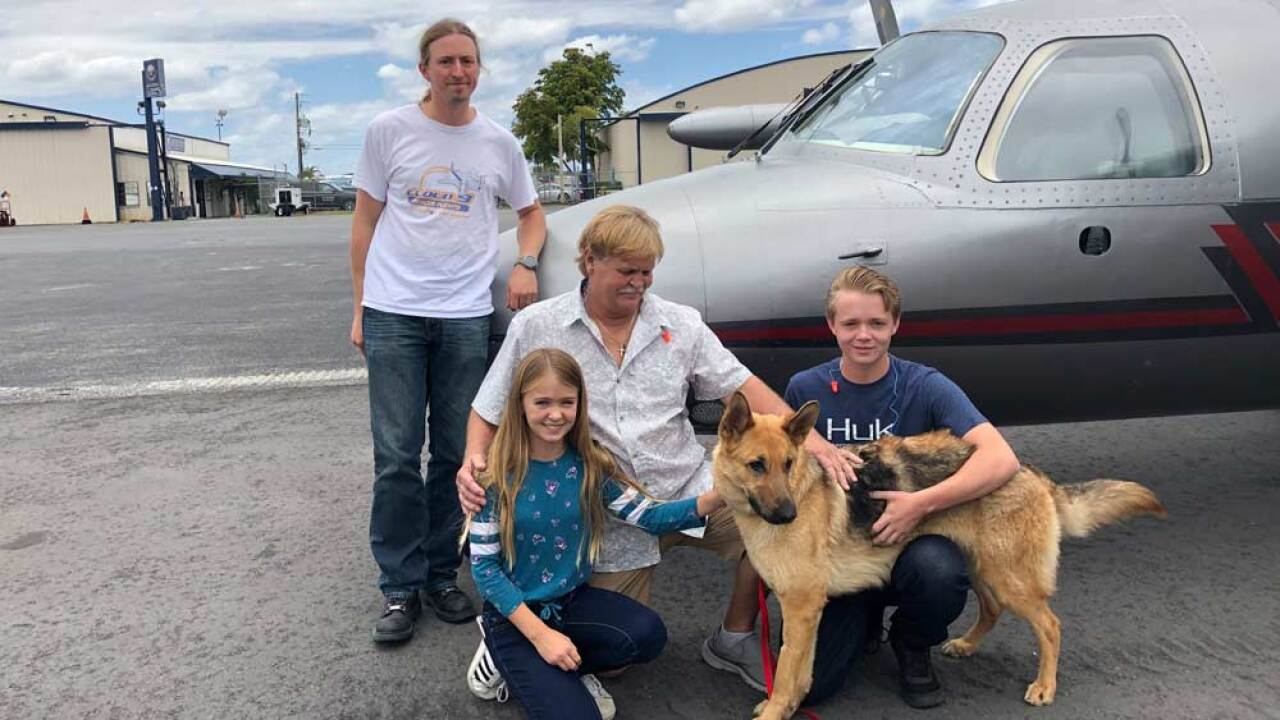 In this photo provided by the Humane Society of Broward County, kneeling from left to right, Chloe, Doug and Chase Peterson greet their long-lost German Shepherd dog Cedar on Saturday, April 20, 2019, at Fort Lauderdale Executive Airport, in Fort Lauderdale, Fla. Cedar, 2, was stolen from her home in Southwest Ranches in 2017 and located this month in Colorado. Standing is pilot Ted DuPuis. (Cherie Wachter/Humane Society of Broward County via AP)