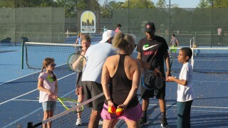 Volunteers work with two children on Oct. 11, 2021, at a tennis clinic for kids who are blind and visually impaired.
