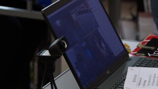 A laptop equipped with a webcam sits on a teacher's desk.